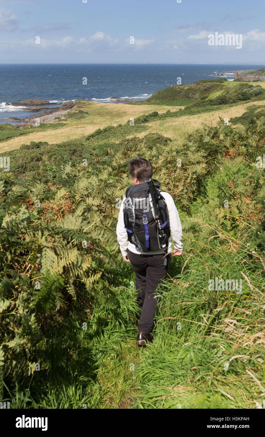 Côte d'Ayrshire, en Écosse. Vue pittoresque d'une dame Walker sur le chemin du littoral de l'Ayrshire, avec Dunure dans l'arrière-plan lointain. Banque D'Images