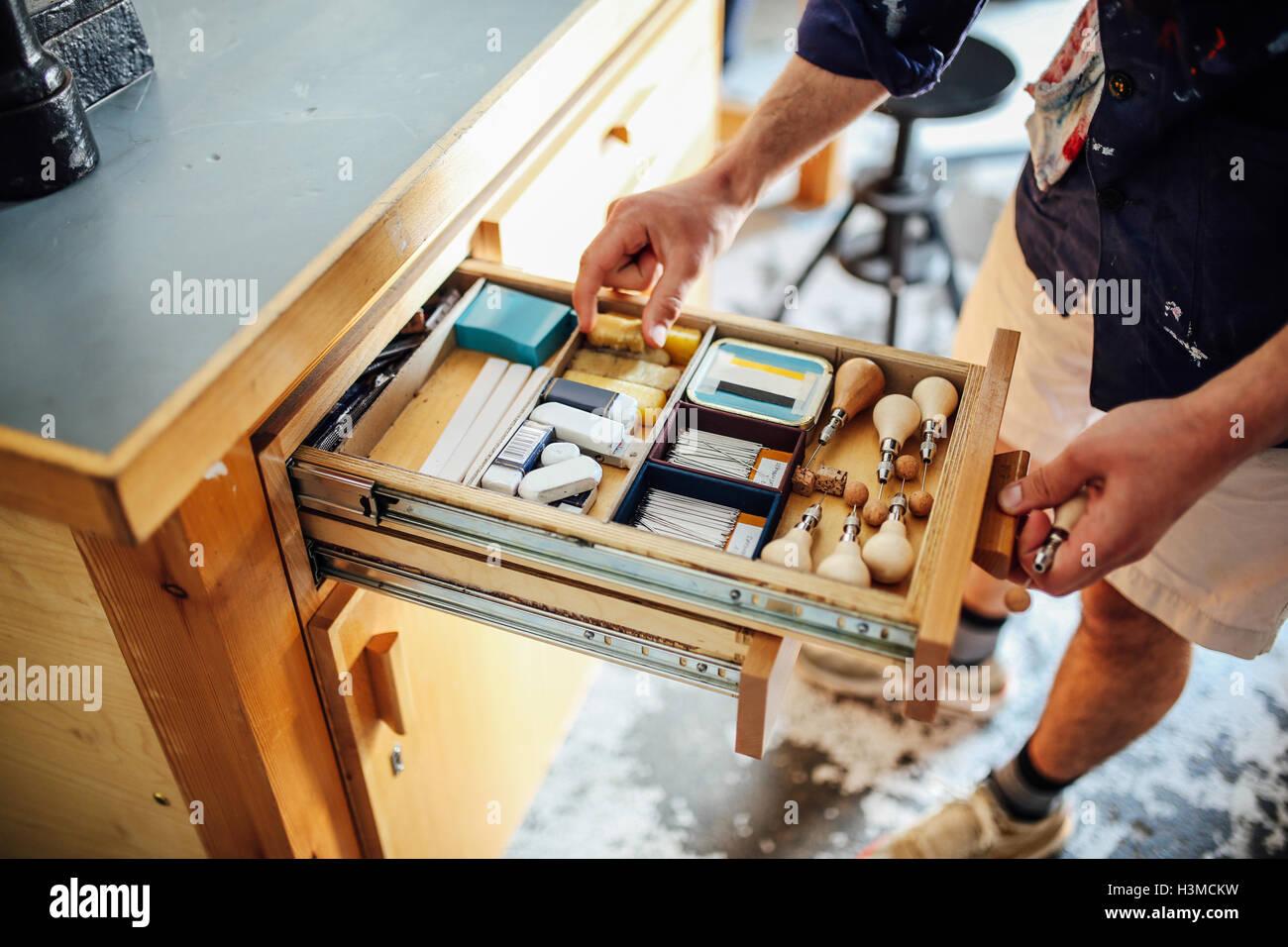 Main dans la main n'ouvrir le tiroir contenant de l'équipement et des matériaux dans l'atelier Photo Stock