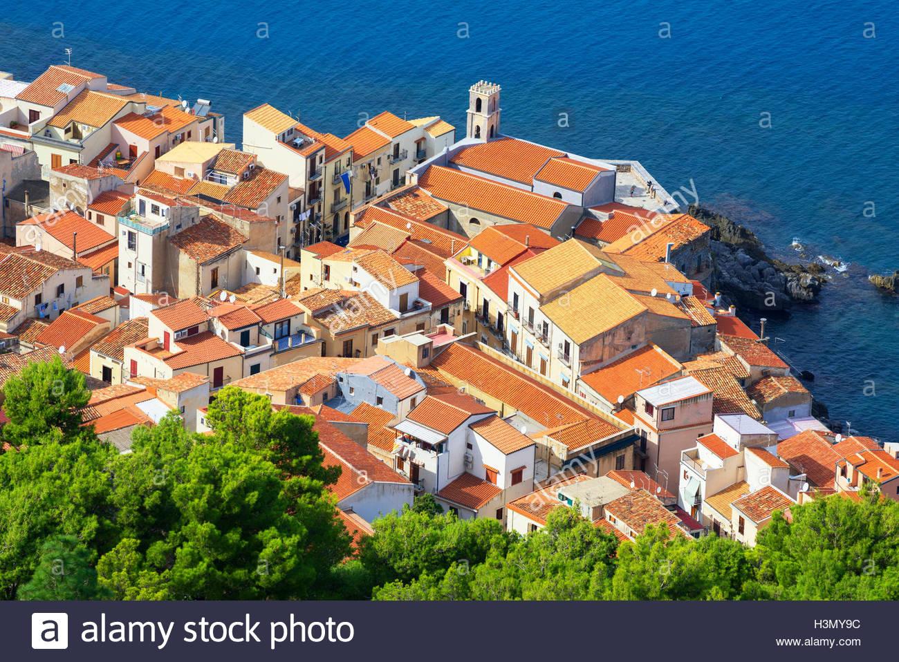 High angle view of Cefalu toits en terre cuite et la côte de la Rocca, Sicile, Italie Photo Stock