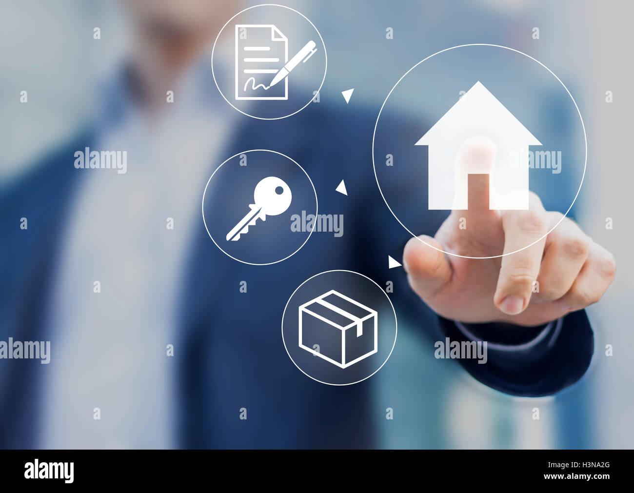 En poussant le bouton main maison sur écran avec contrat hypothécaire, les clés et les boîtes Banque D'Images