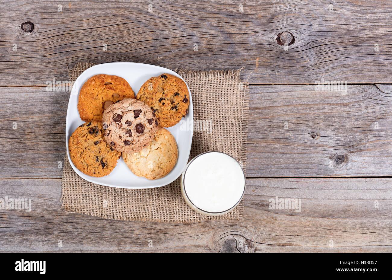 Vue aérienne d'une variété de biscuits fraîchement cuits au four sur une serviette avec un verre de lait. Banque D'Images