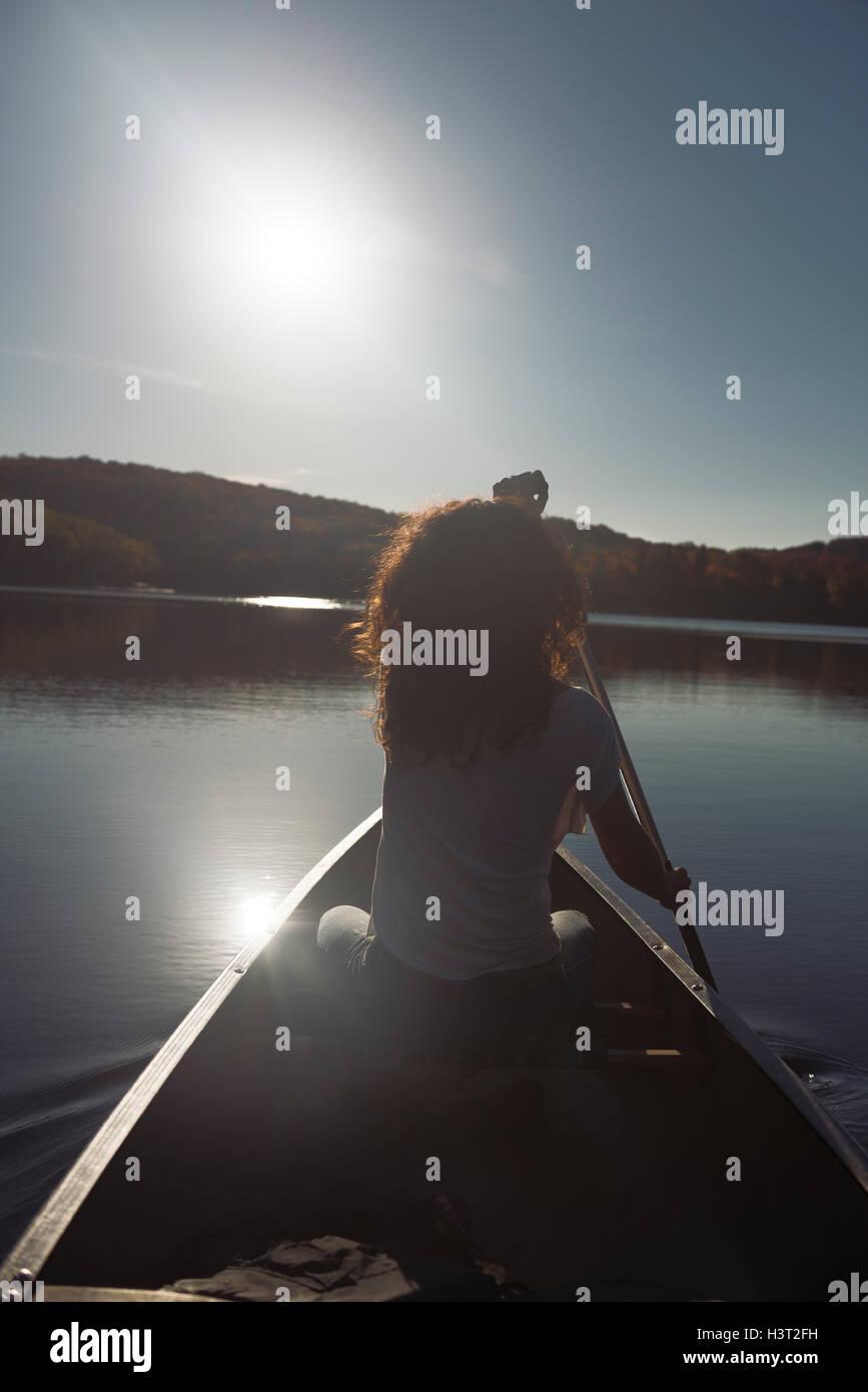Jeune femme canoë sur un lac à l'automne. Le parc provincial Arrowhead, Muskoka, Ontario, Canada. Photo Stock