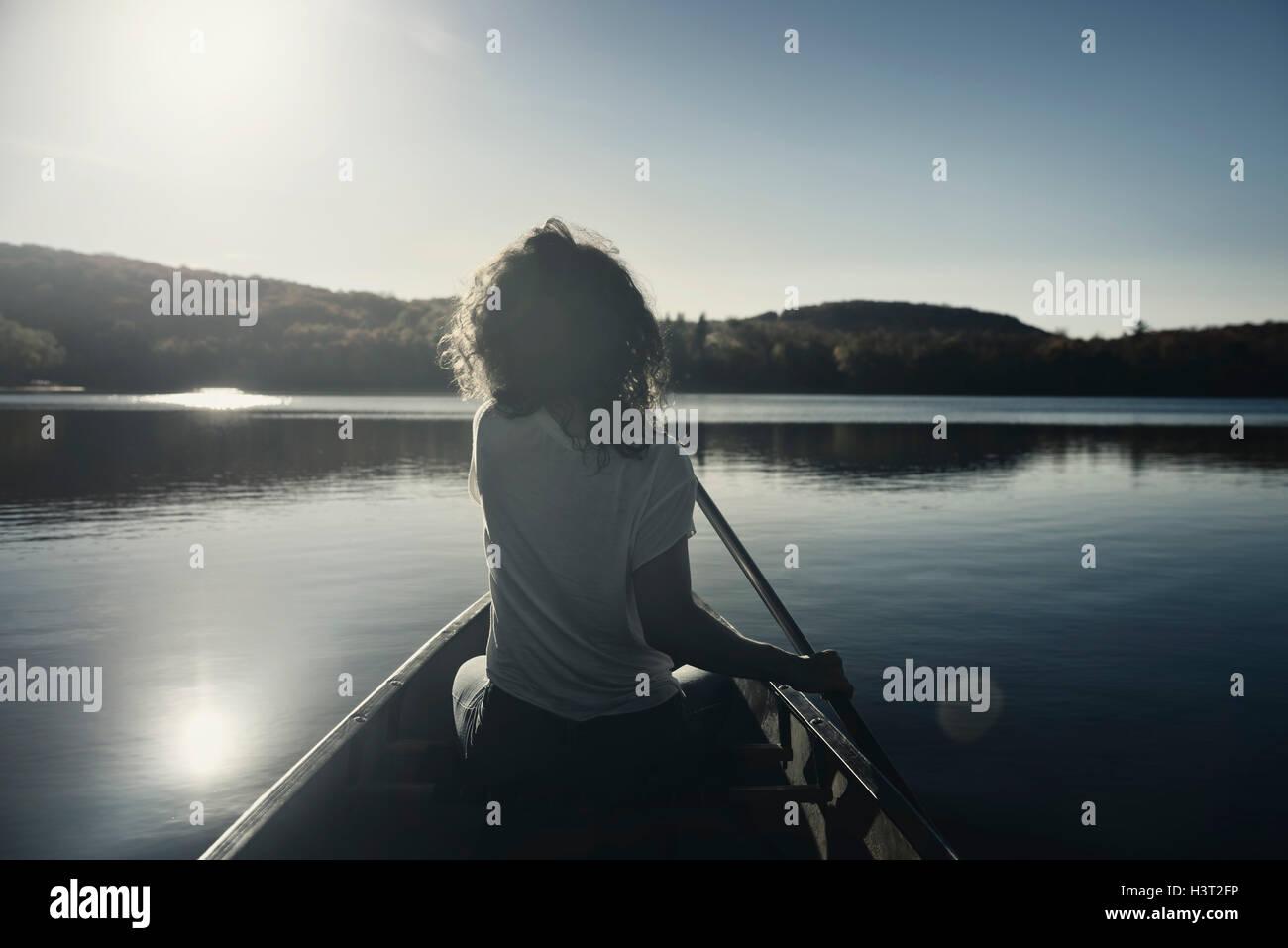 Jeune femme canoë sur un lac à l'automne. Muskoka, Ontario, Canada. Photo Stock