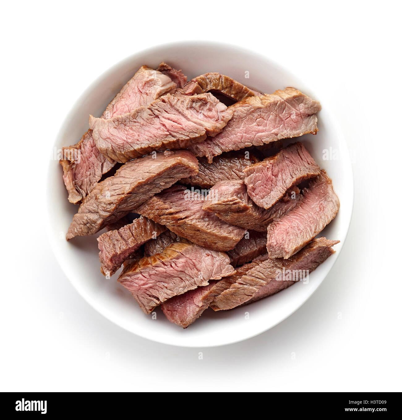 Bol de tranches de bœuf grillé isolé sur fond blanc, vue du dessus Photo Stock