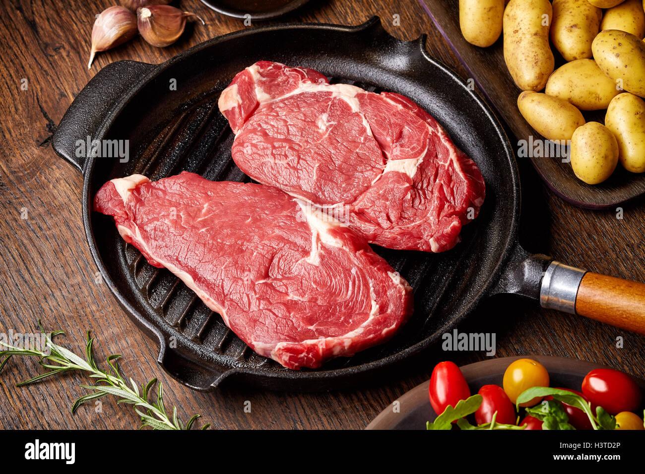 Steak de boeuf cru sur gril, pommes de terre, les épices et les tomates de table en bois Photo Stock