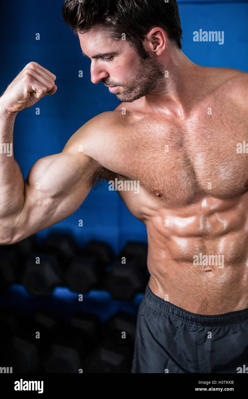 Athlète flexing muscles torse nu dans la salle de sport Photo Stock