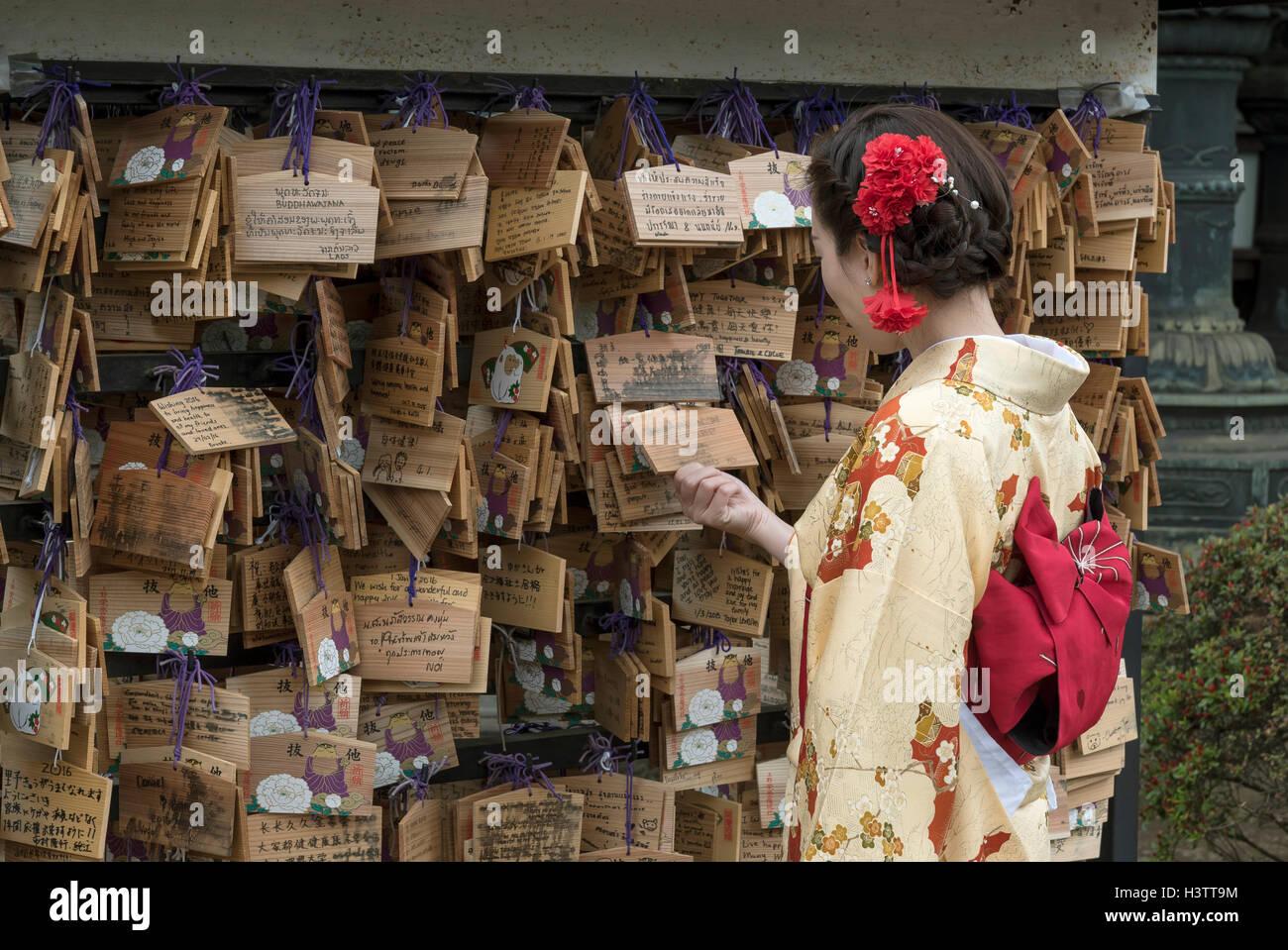 Femme vêtue de kimono traditionnel ressemble à l'Ema souhaitent des plaques lors d'Ueno Toshogu, Photo Stock