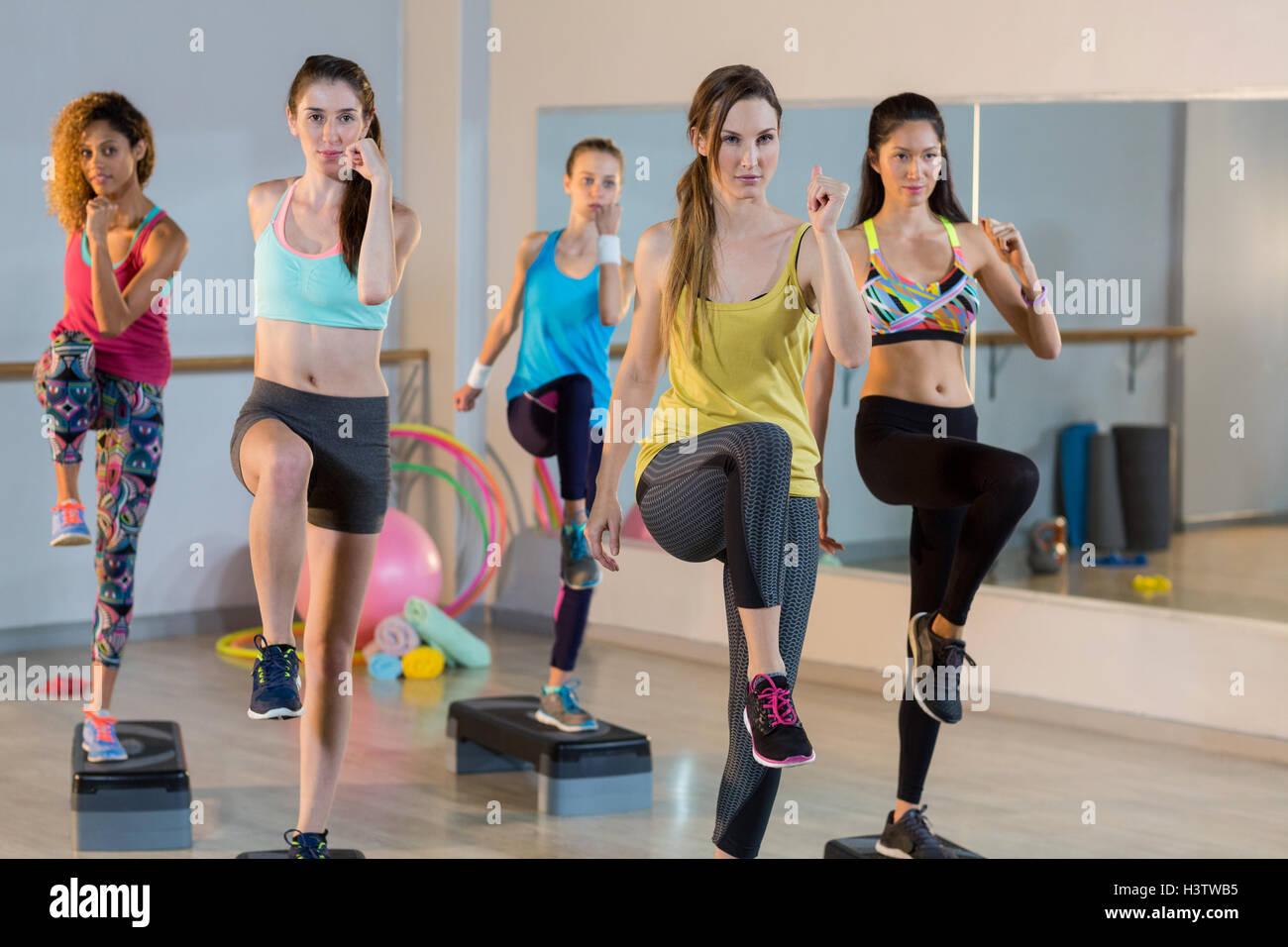Groupe de femmes exerçant de pas-à-pas aérobie Photo Stock