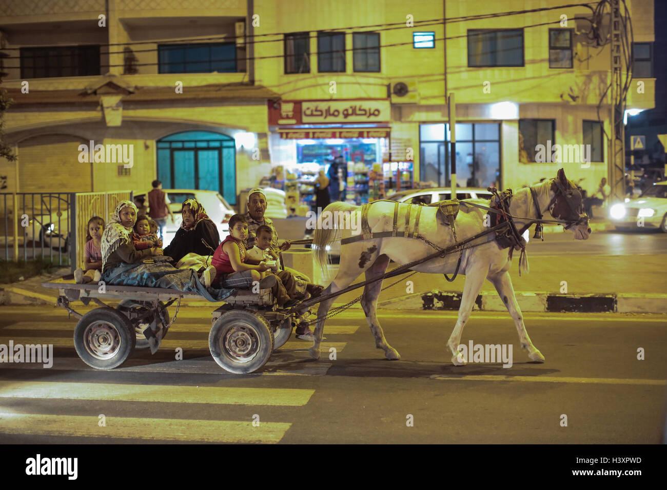 Un cheval tirant une charrette transportant une famille dans la ville de Gaza. À partir d'une série Photo Stock