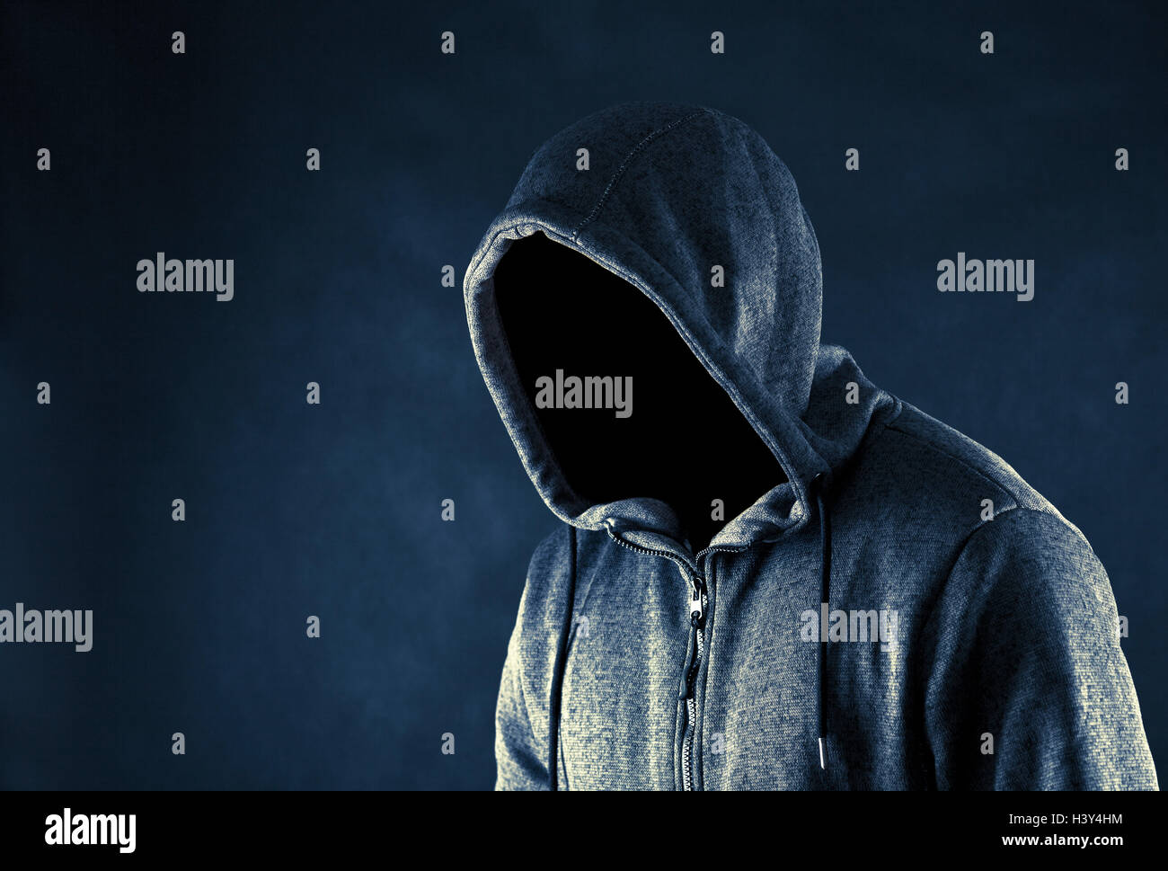 Homme cagoulé dans le noir Banque D'Images