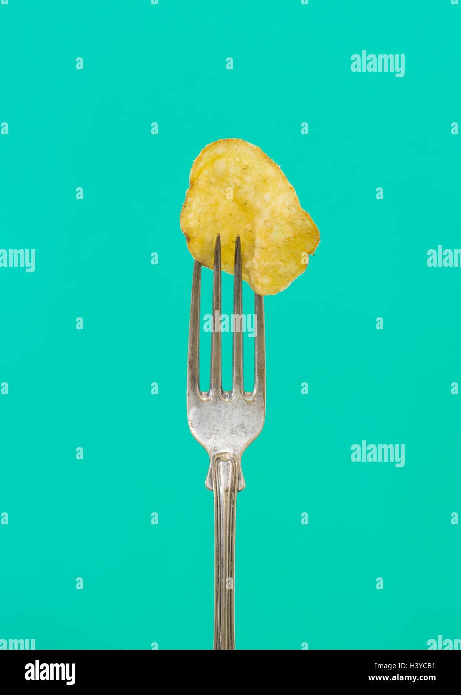 L'une croustille sur fourche. Close up de salé et gras collation. Concept de la mauvaise alimentation. Banque D'Images