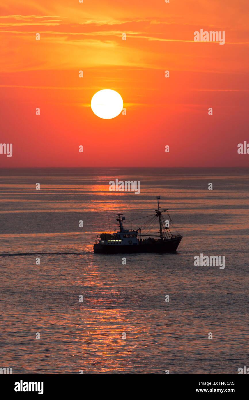 Un chalutier de pêche sur la mer du Nord au large de la côte de la Belgique au coucher du soleil. Banque D'Images