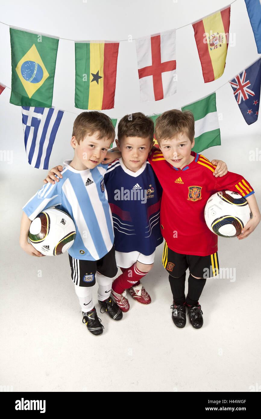 Les garçons, trois, maillots de football, ballons de football, photo de groupe, les drapeaux, Banque D'Images