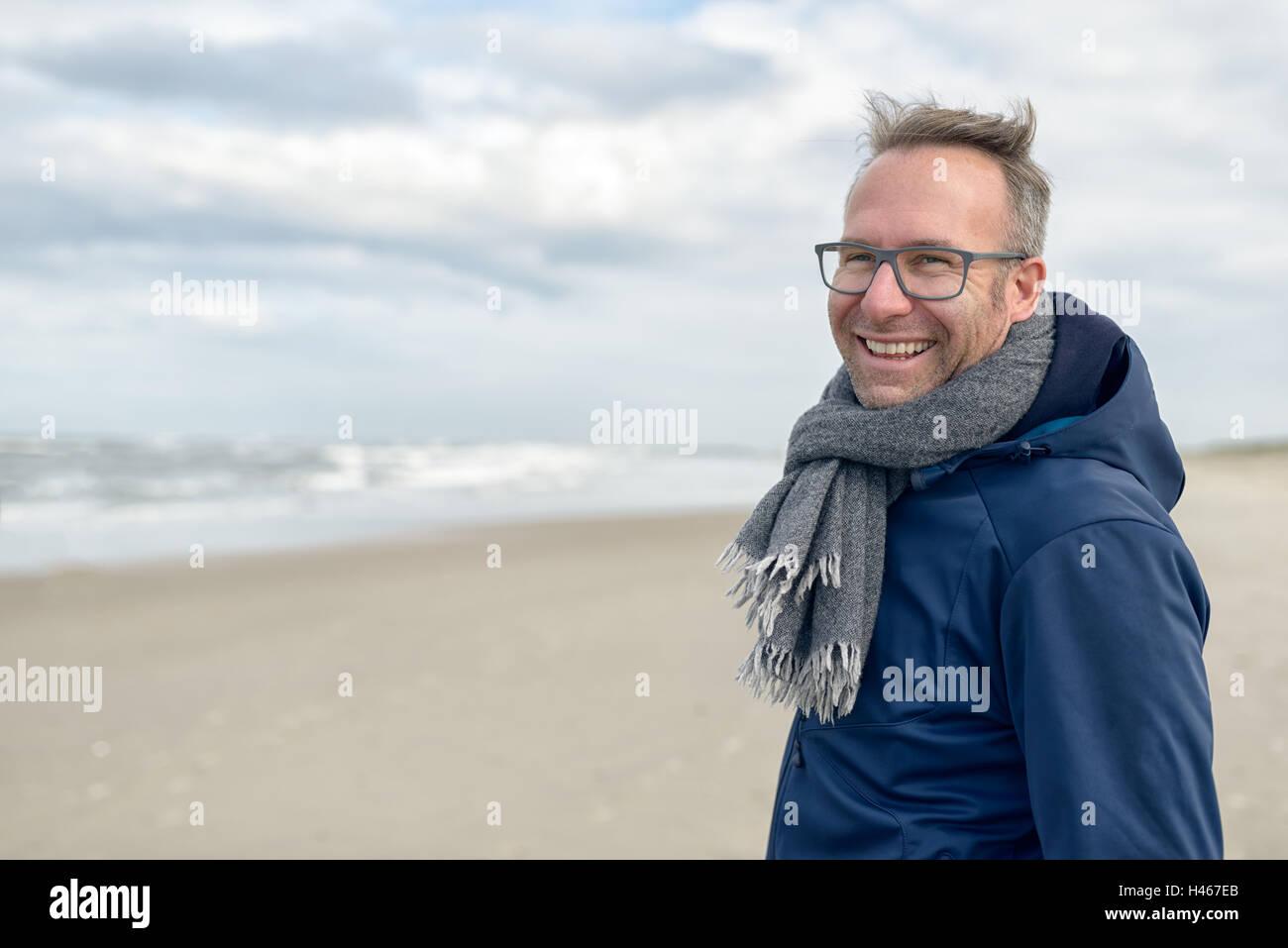Smiling middle-aged man portant des lunettes et une écharpe en laine tricoté debout sur une plage déserte Photo Stock