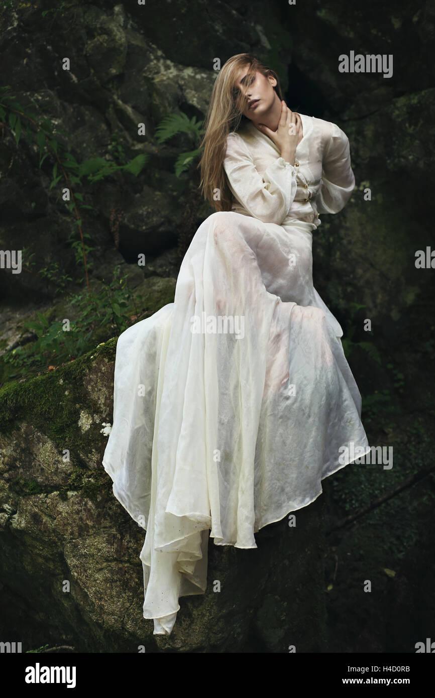 Belle femme posant sur des pierres et de la mousse. Atmosphère de rêve Photo Stock