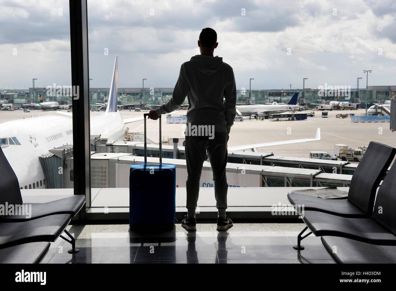 Un adolescent est en attente sur un aéroport pour départ Photo Stock