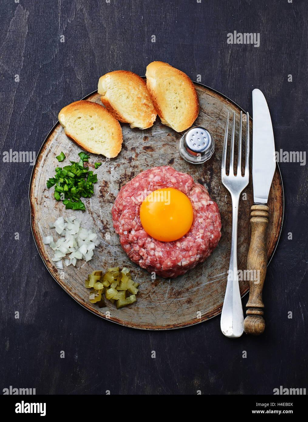 Tartare de boeuf frais avec l'oeuf, cornichon et l'oignon. Selective focus Photo Stock
