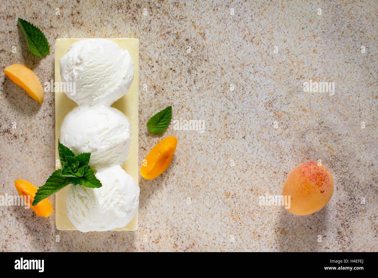 La crème glacée avec une pêche dans une forme une boule, la place pour votre texte. Photo Stock