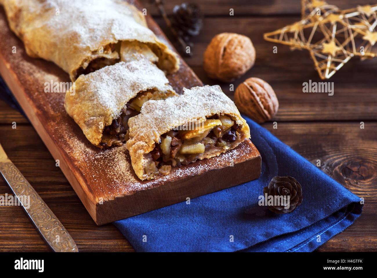 Pâtisserie Maison de Noël. Strudel aux pommes (tarte) avec les raisins secs, les noix et le sucre en poudre Photo Stock