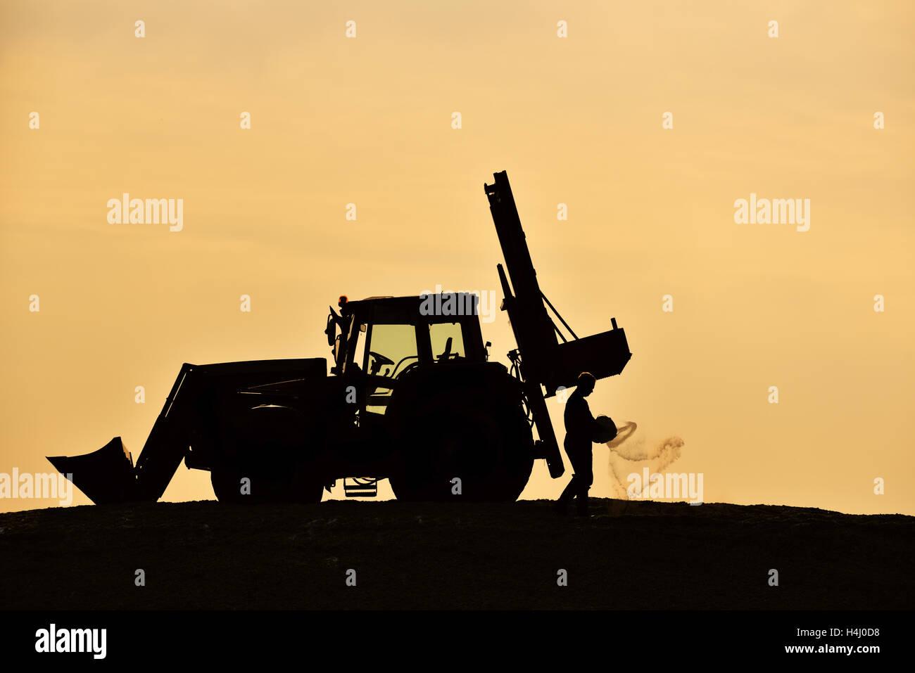 Le tracteur et l'Agriculteur Agriculteur Silhouettes, saupoudrer les tas d'ensilage, pendant le crépuscule. Photo Stock