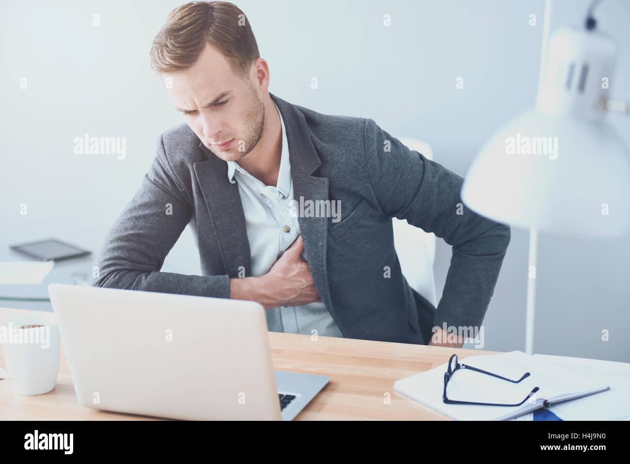 Beau jeune homme souffrant de douleur par le lieu de travail. Photo Stock
