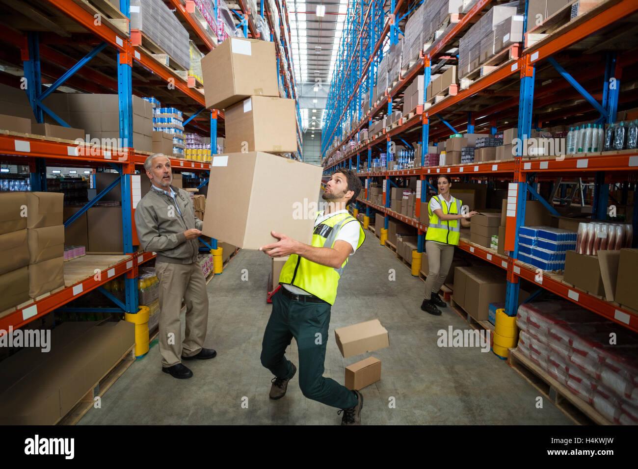 Perdre son travailleur équilibre tout en transportant des boîtes de carton Photo Stock