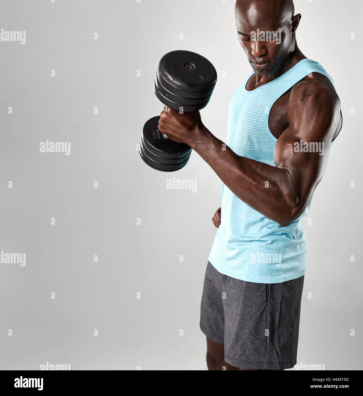 Fit young African man exercising with dumbbells contre fond gris. Modèle homme noir musclé soulever de Photo Stock