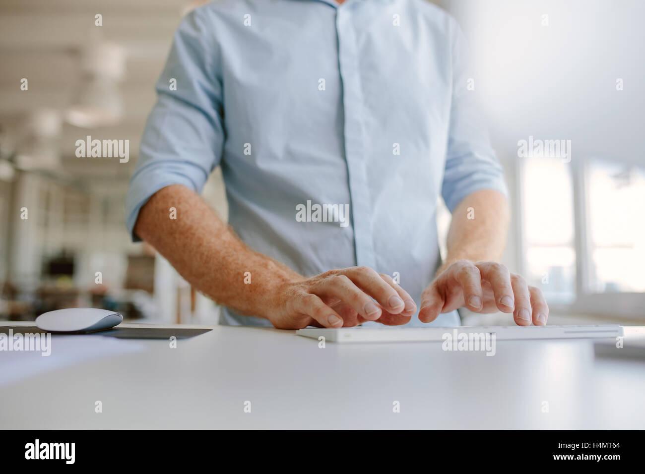 Les mains de la saisie sur clavier d'ordinateur. Cropped shot jeune homme travaillant sur ordinateur tout en Photo Stock