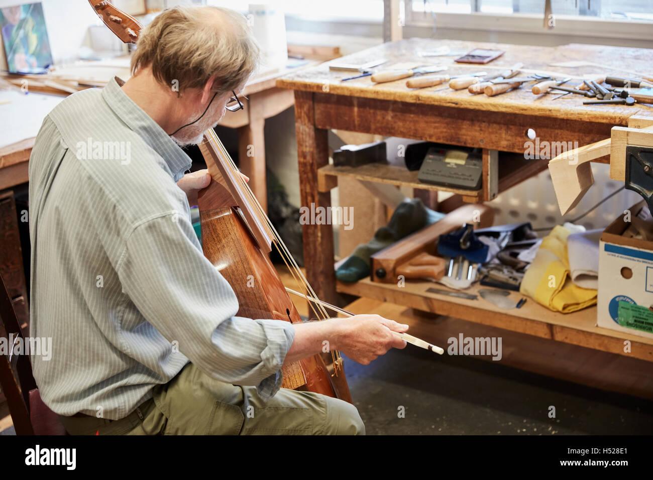 Un luthier à son atelier à l'instrument avec un archet, d'optimisation et de finition. Photo Stock