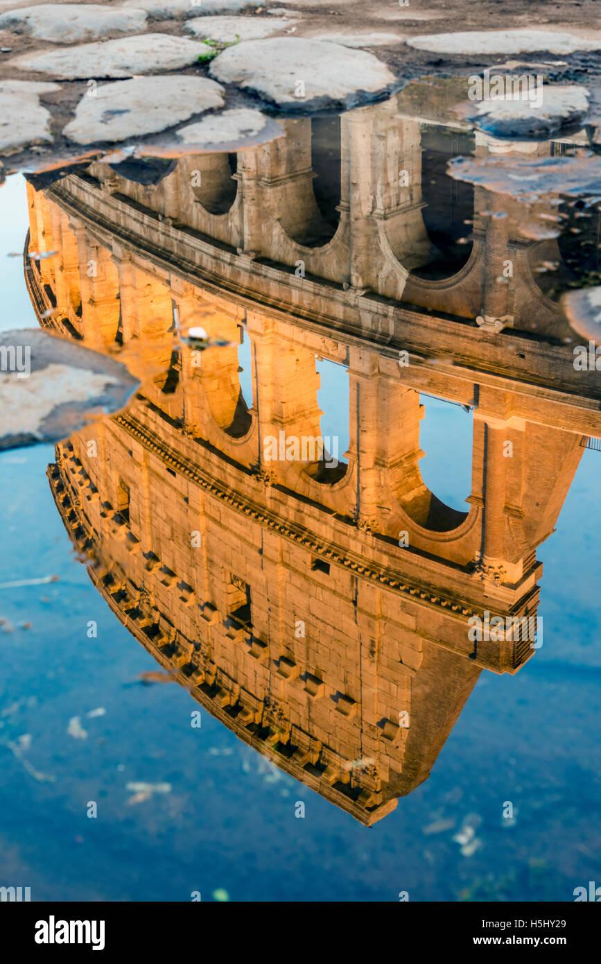 Colisée ou Coliseum reflété dans une flaque d'eau au coucher du soleil, Rome, Latium, Italie Photo Stock
