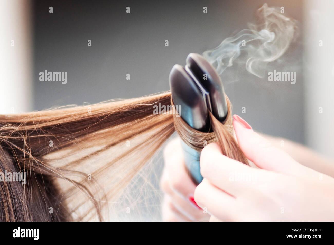 Coiffure L'application d'un fer à repasser tout droit sur une femme Coiffure Photo Stock
