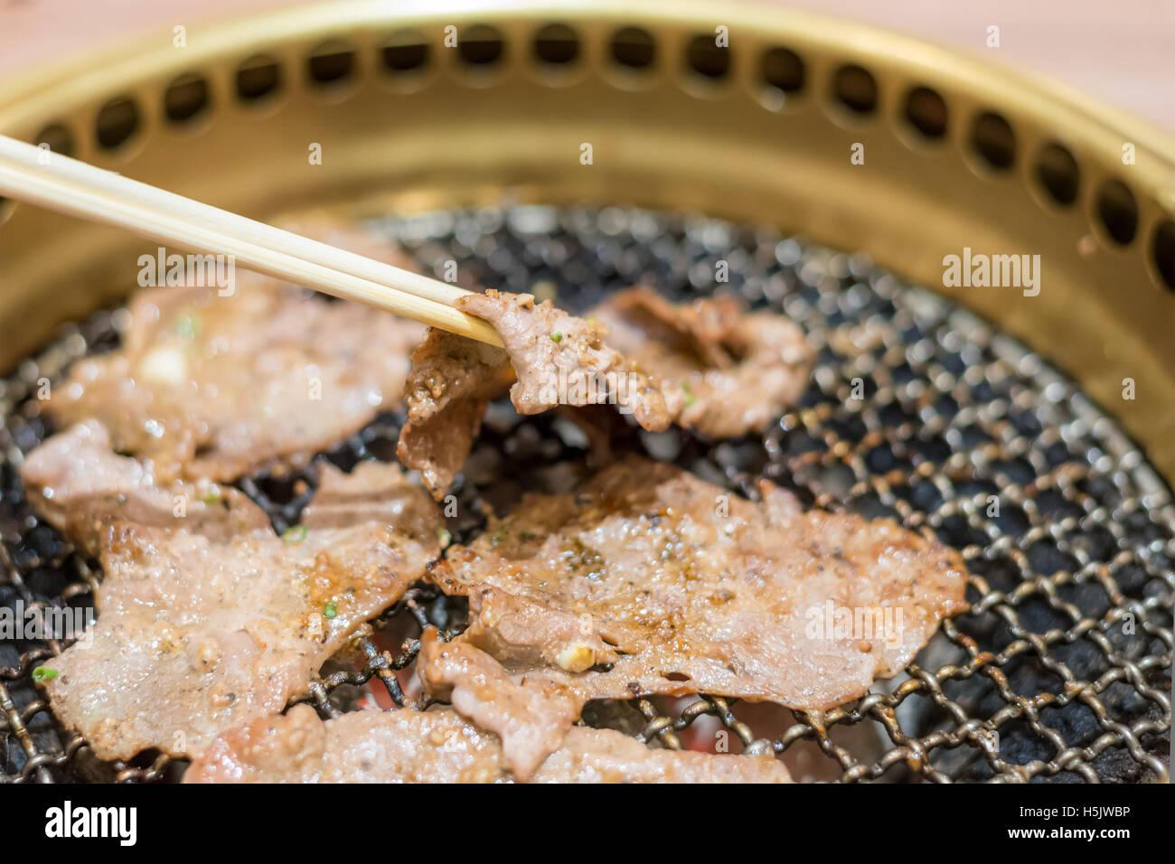Tranche de porc steak la cuisson au grill au charbon. Close up au steak de porc chopstick. coupe Photo Stock