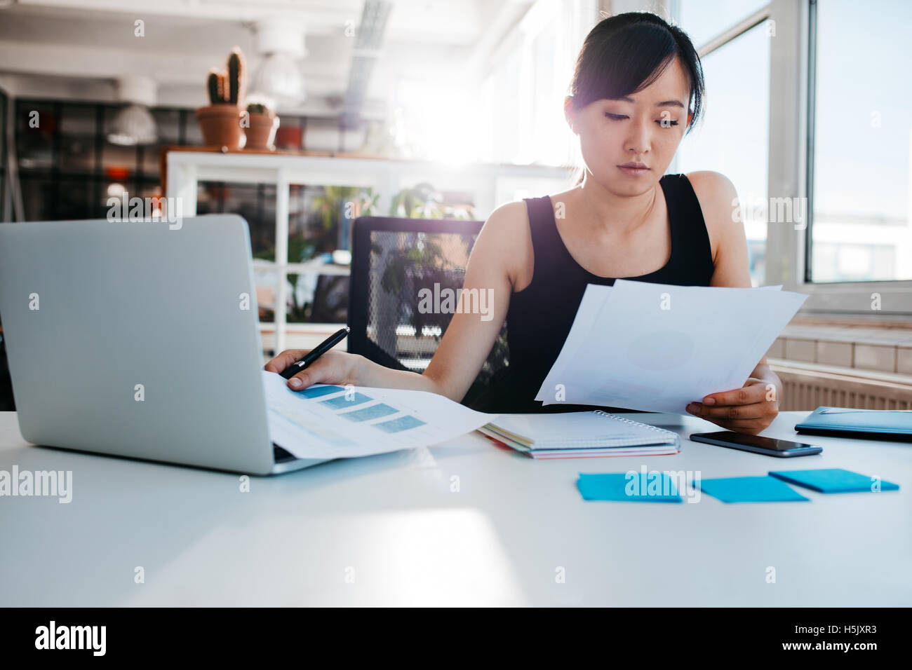 Portrait of young asian woman lire des documents à son bureau. Businesswoman typing dans son milieu de travail. Photo Stock