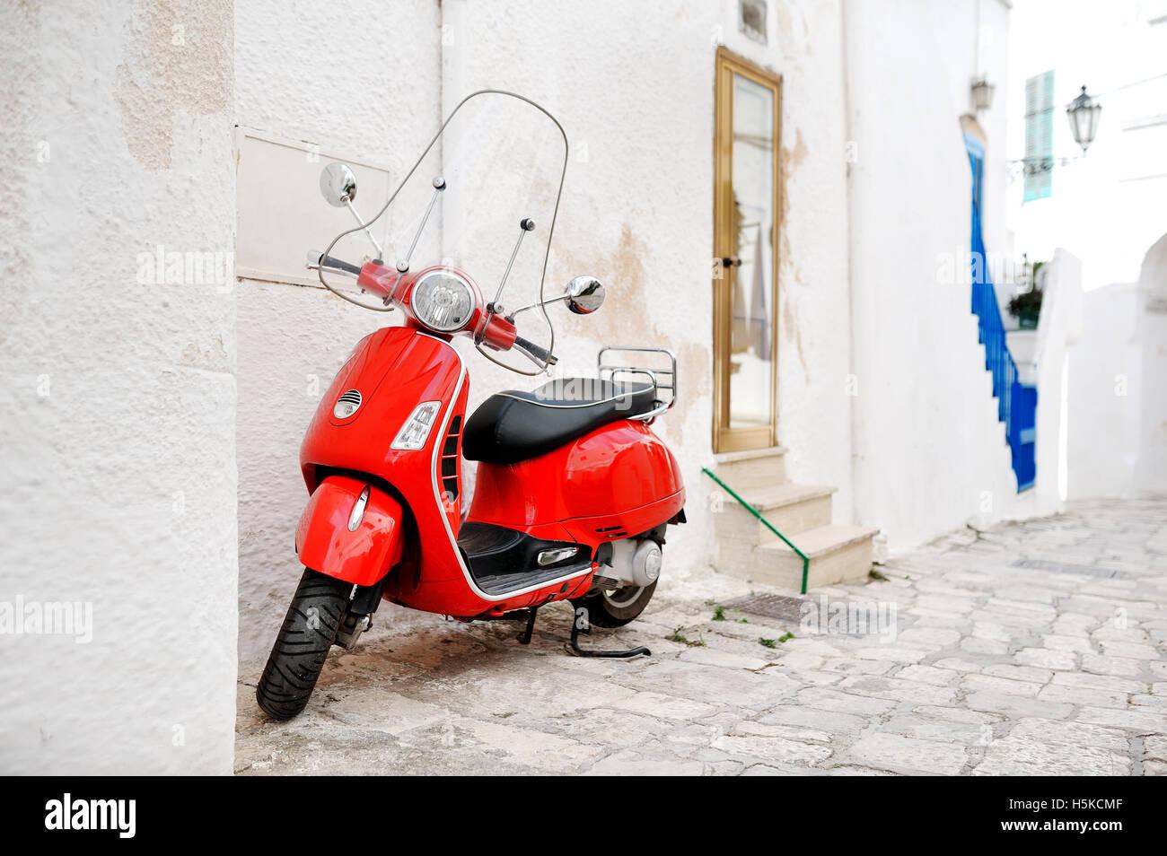Pouilles, Italie - scooter rouge dans une ruelle de la ville blanche Ostuni Banque D'Images