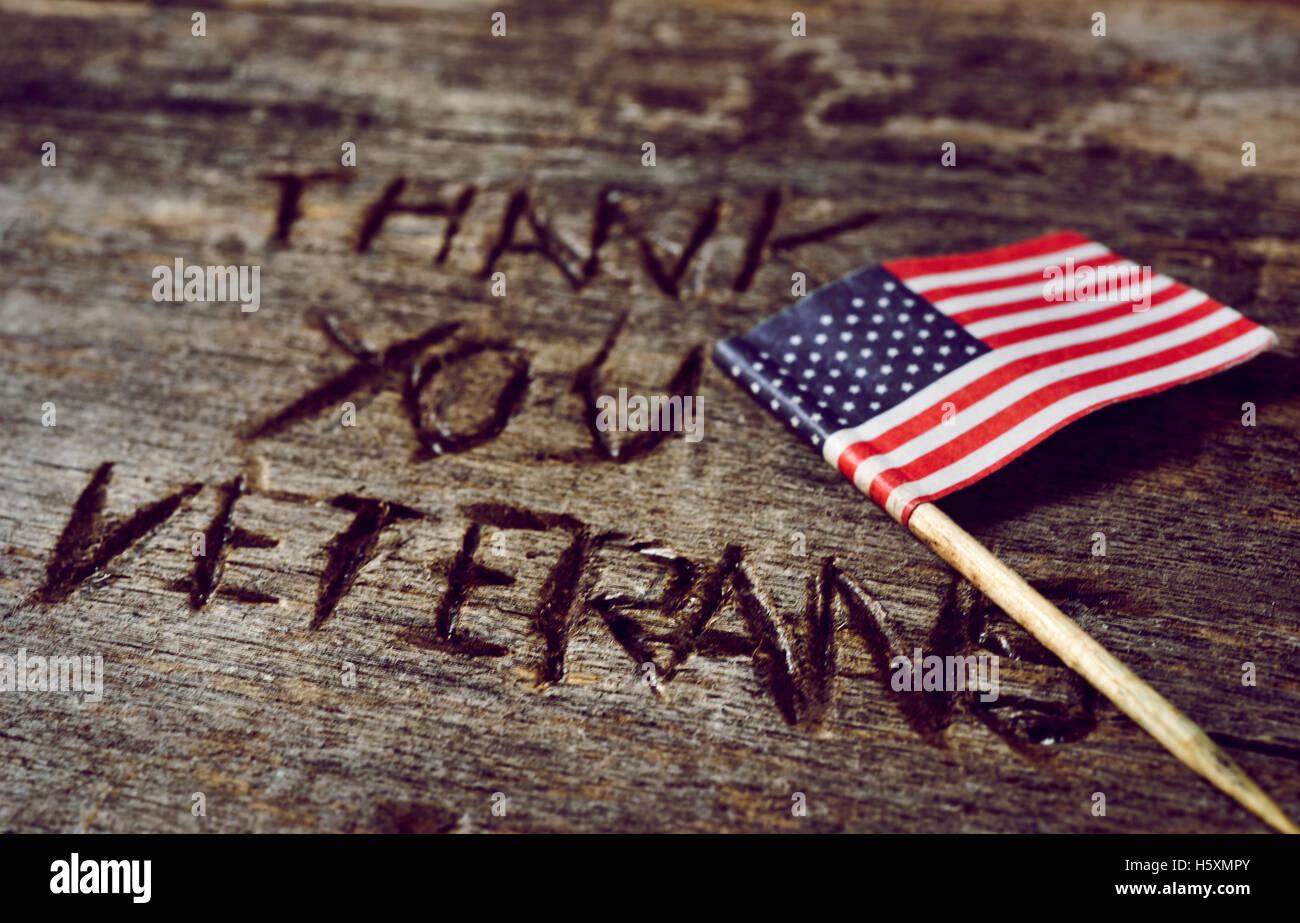 Le texte des anciens combattants vous remercie sculpté dans une surface en bois rustique et d'un drapeau Photo Stock