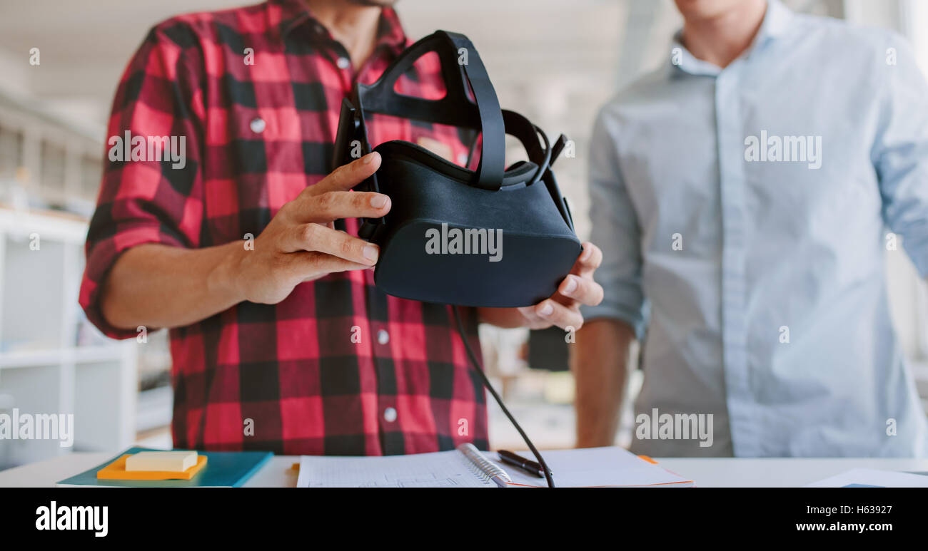 Cropped shot de deux jeunes hommes l'essai casque de réalité virtuelle à l'office. Les hommes Photo Stock