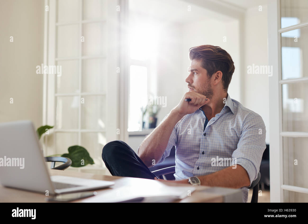 Shot of young man sitting at table à l'écart et la pensée. Thoughtful woman home office. Photo Stock