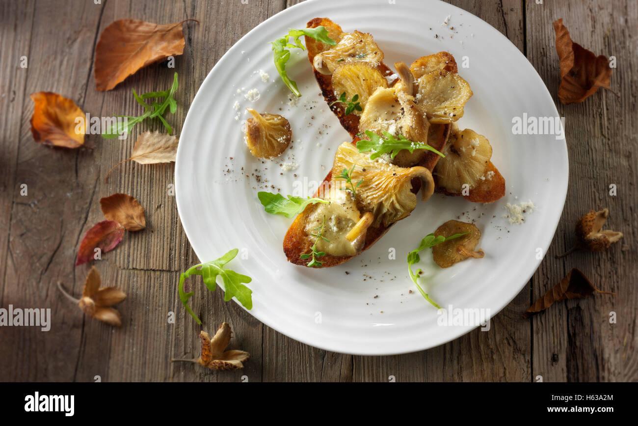 Pleurotes jaunes sautés dans du beurre et servi sur toast au levain avec la roquette sauvage Photo Stock