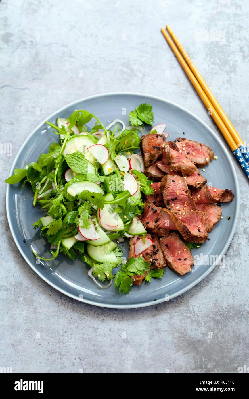 Salade de bœuf asiatique avec le concombre et salade d'herbes et de graines de sésame noir et blanc Photo Stock