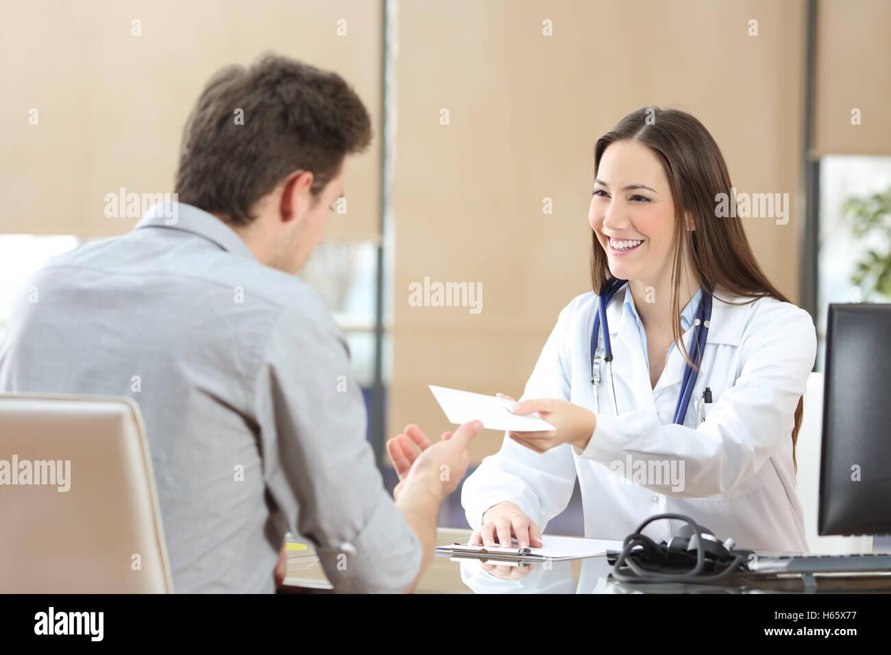 Femme médecin heureux de donner une ordonnance à son patient à une consultation. Banque D'Images