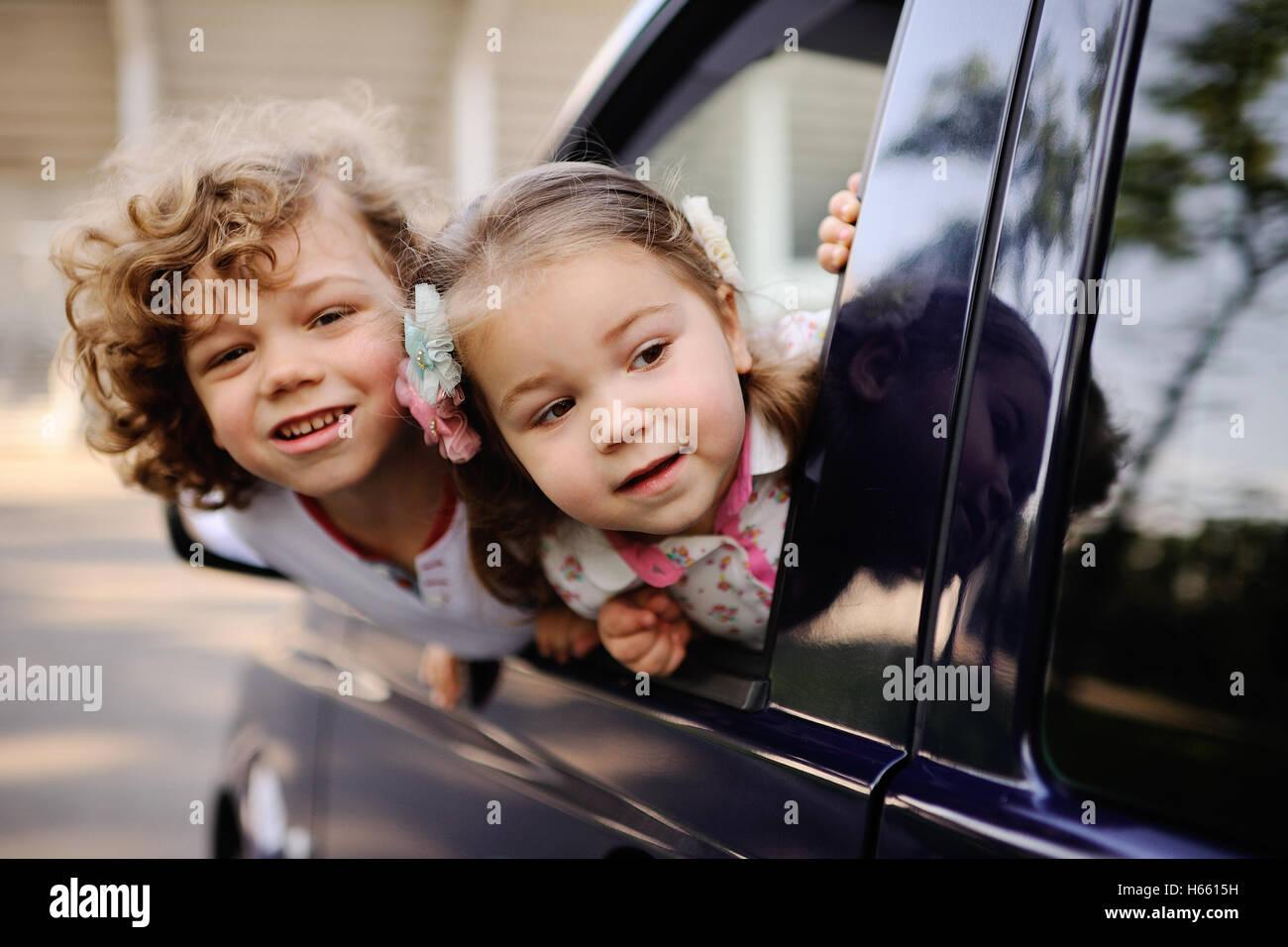 Les enfants donnent de la fenêtre d'une voiture Banque D'Images