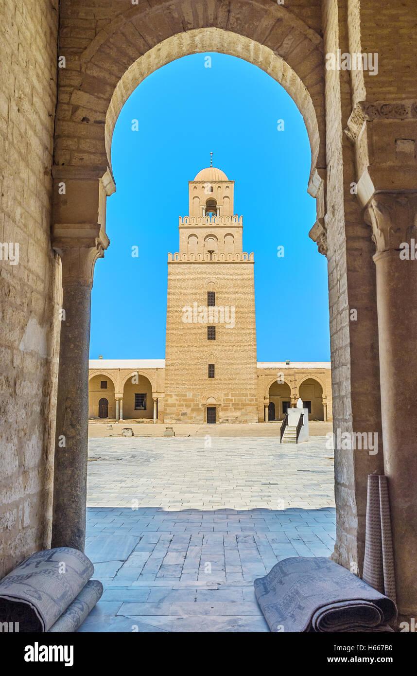 La vue sur l'ancien minaret de la Grande Mosquée à travers l'arche de sa cour, Kairouan, Tunisie. Banque D'Images