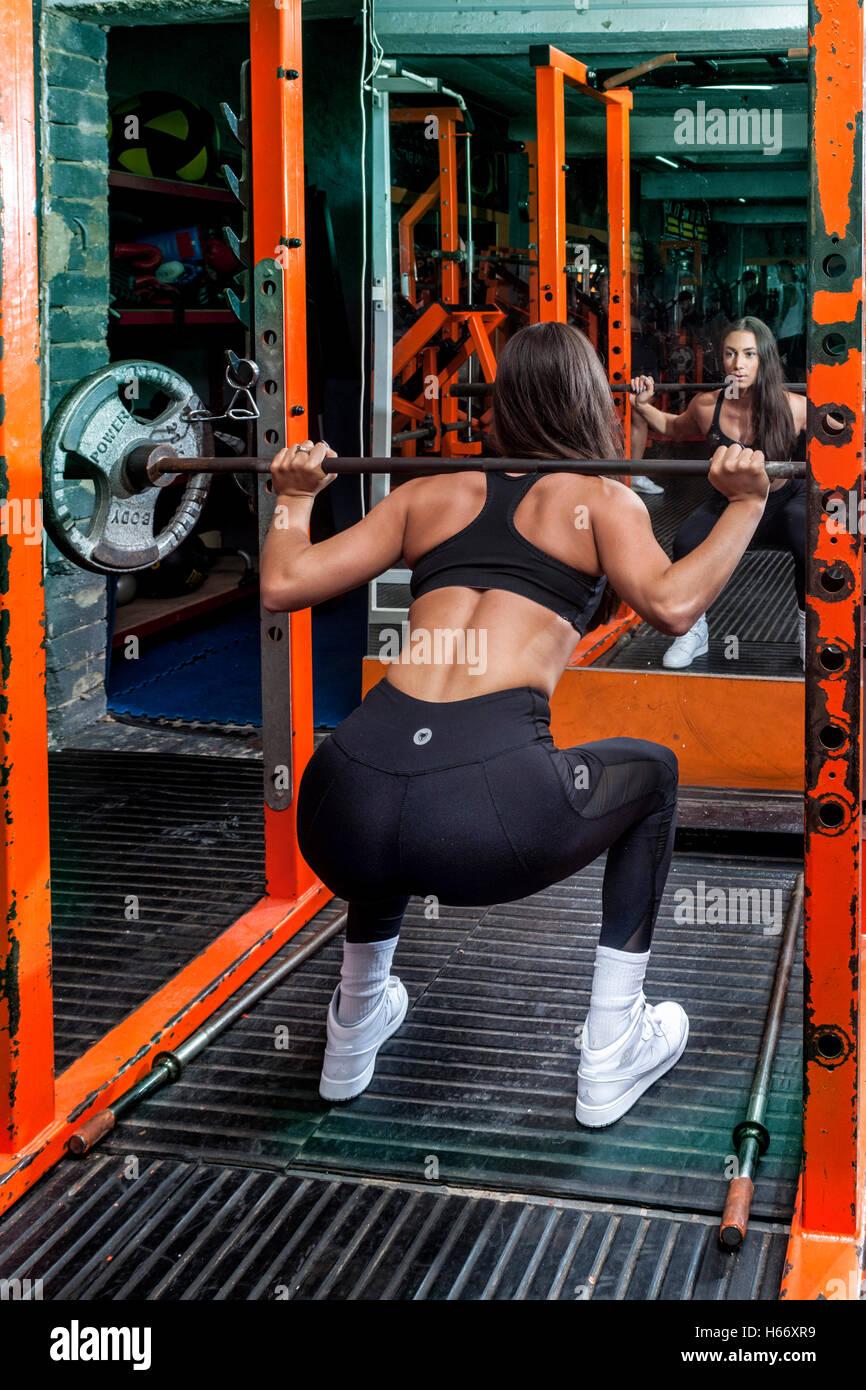 Femme dans la salle de sport la levée de poids Photo Stock