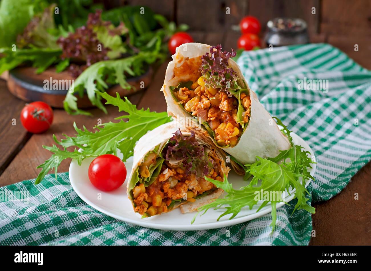 Burritos wraps avec la viande hachée et de légumes sur un fond de bois. Photo Stock
