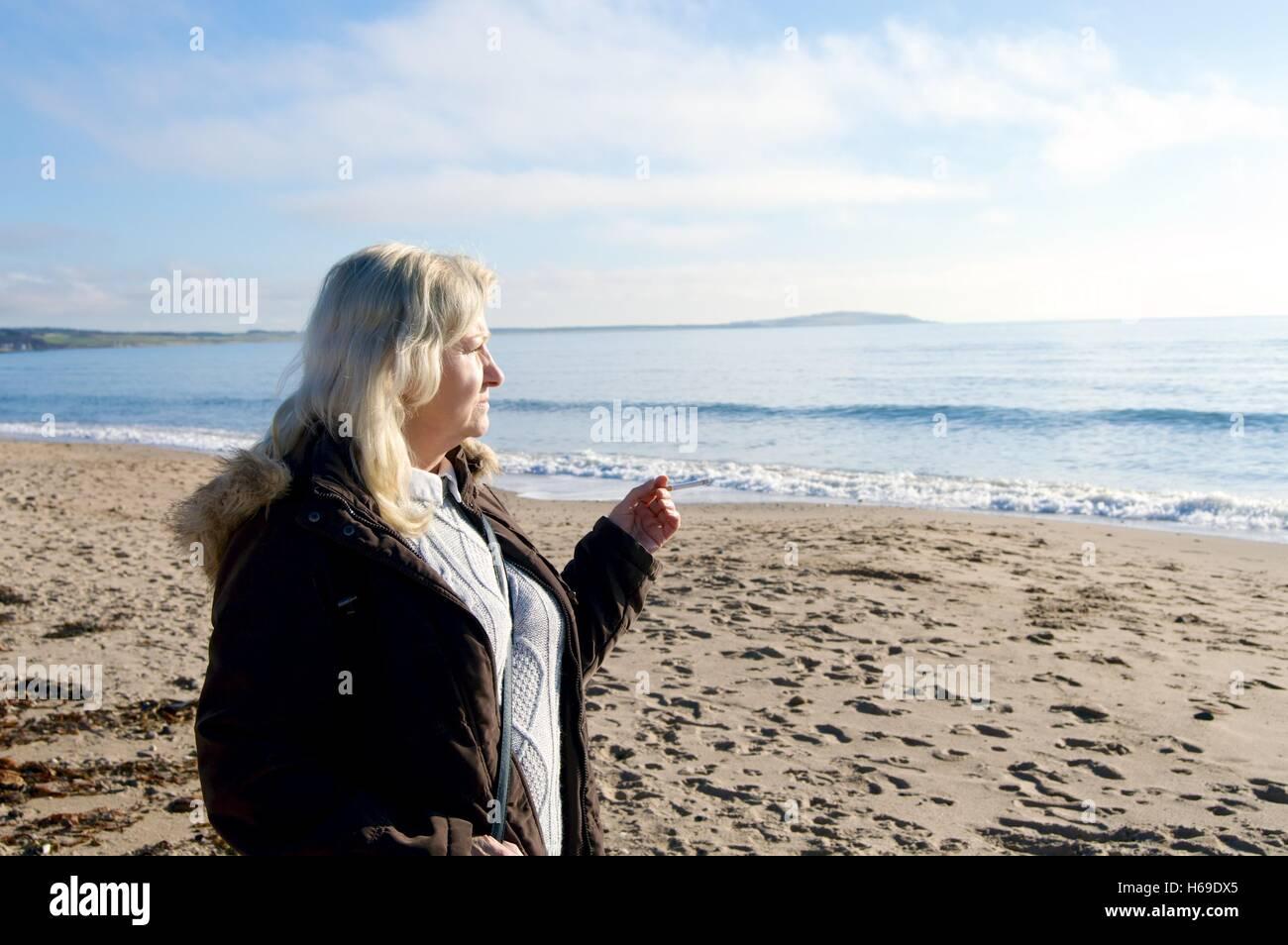 Femme de fumer une cigarette sur la plage Leven Ecosse Banque D'Images