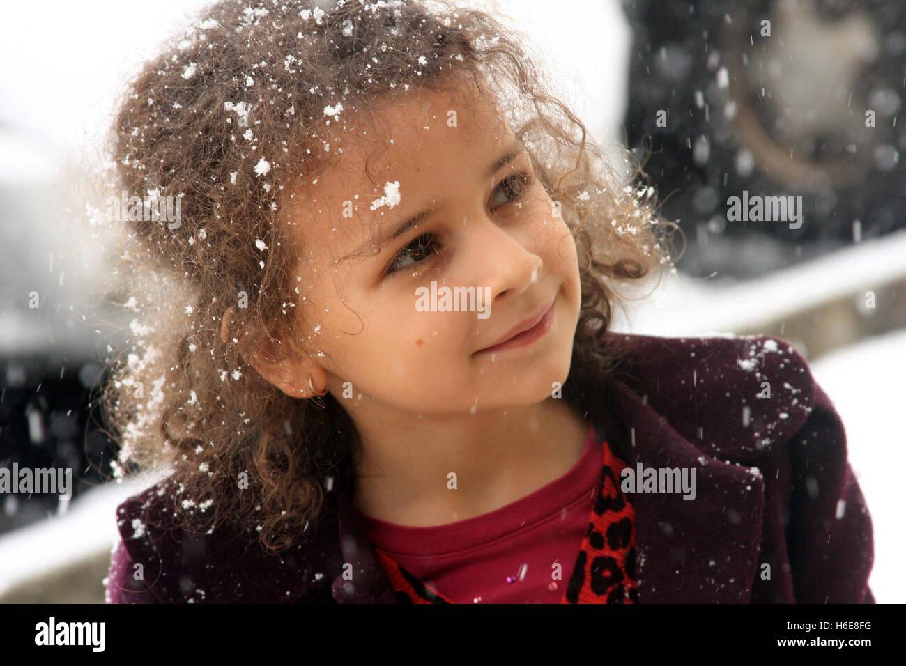 Petite fille heureuse pour la neige tombant autour de Photo Stock