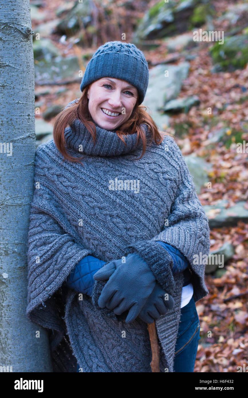 Une femme glamour de la randonnée à travers les bois en automne automne vêtu d'un poncho en laine Photo Stock