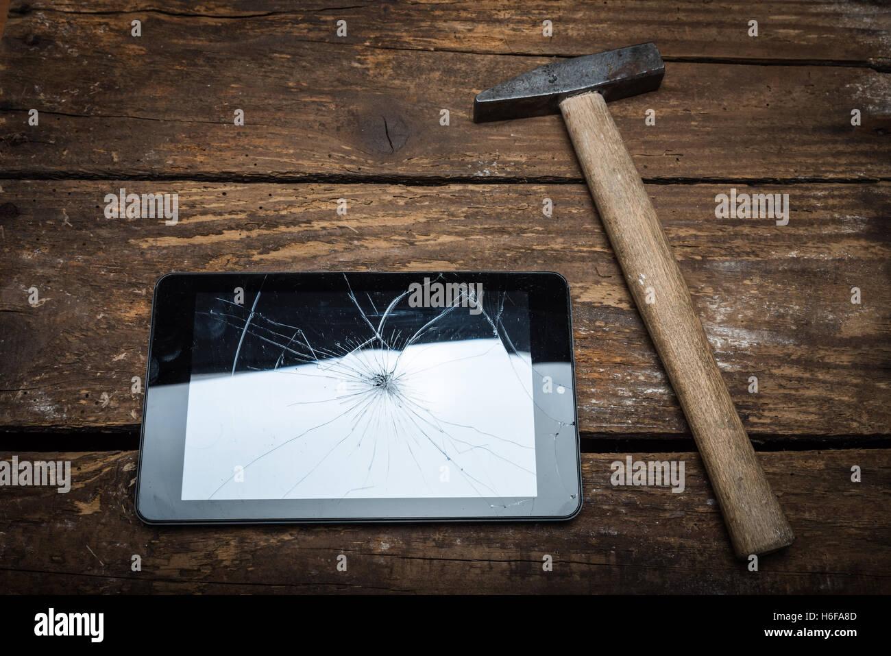Marteau et d'un comprimé sur la table en bois avec du verre brisé. Banque D'Images