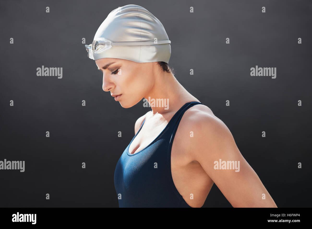 Vue latérale du fit young female swimmer sur fond noir. Femme Fitness en maillot de concentration. Photo Stock