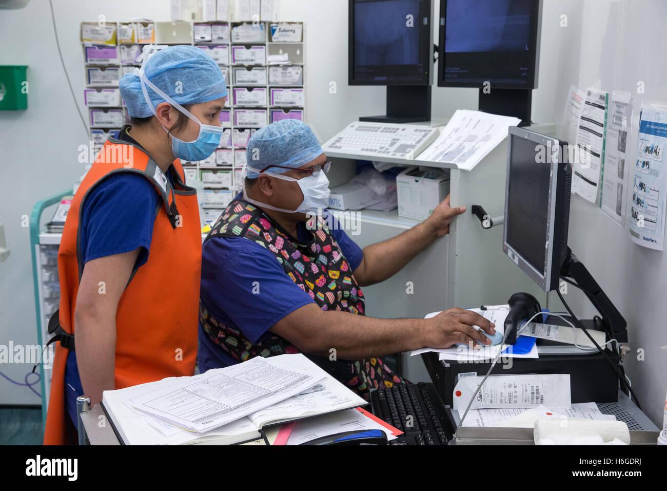 Deux techniciens de théâtre vérifie les données des patients sur l'écran au cours d'une Photo Stock